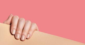 Mão de mulher posicionada em um móvel de madeira realça suas unhas fortes e saudáveis