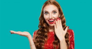 Mulher sorridente mostra suas unhas fortalecidas e seus cabelos volumosos, frutos da ingestão de cisteína