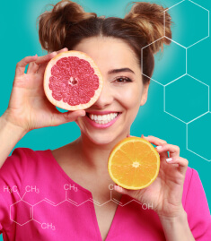 Mulher sorrindo e segurando duas metades de laranja, uma à frente do olho direito. A imagem reforça a presença das vitaminas a, c, d e e em Spax Hair & Nails.