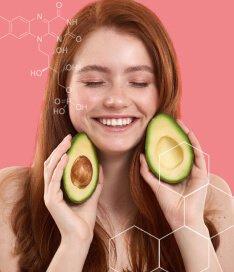 Mulher ruiva com os olhos fechados, sorrindo e segurando duas metades de abacates nas mãos. A imagem reforça a presença das vitaminas do complexo b em Spax Hair & Nails.